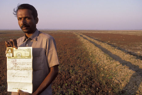 Bangladesh | A smallholder shows his deeds of agricultural land that has been claimed and amalgamated into that of a larger landowner / Peter Barker - Panos pictures