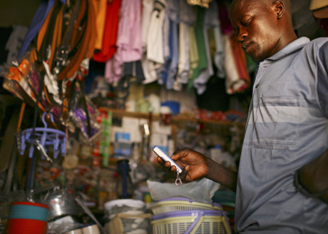 Uganda | A man in a shop uses his mobile phone, which can be used to pay for transactions / Abbie Trayler-Smith - Panos Pictures