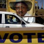 Uganda | One of President Yoweri Museveni's military bodyguards passes a billboard at an election rally during the last Ugandan election in 2006 / Sven Torfinn - Panos Pictures
