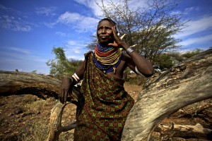 Etukoit, a Turkana woman, sits on a fallen tree in Kaaleng