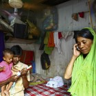 Shahera Begum makes a telephone call while her son Najmul Islam (19 months) plays with a toy guitar with his father in Dhaka, Bangladesh. By harnessing the potential of mobile telephones and other ICTs, Panos London helps improve access to health services - gmb akash | panos pictures