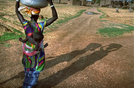 A woman walks home with a bucket of water on her head and a child on her back. She has to walk more than a kilometre between the well and home several times a day. Traditionally, water transportation is a woman's job, one of such importance that many girls are kept from attending school - Dieter Telemans | Panos Pictures