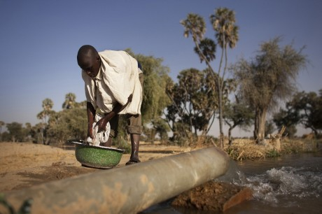 A boy washes clothes in an irrigation canal filled with water pumped from the River Yobe, which feeds Lake Chad. The lake is drying up, due largely to desertification as the Sahara advances southward | Panos Pictures