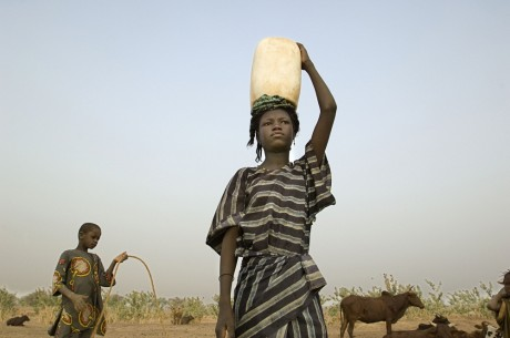 A girl carries water on her head in the village of Intedeyne, Mali - Ami Vitale | Panos Pictures