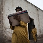 A student heads home with his books from the Mohripur Government Primary School. The school has no desks and no electricity - Zackary Canepari | Panos Pictures