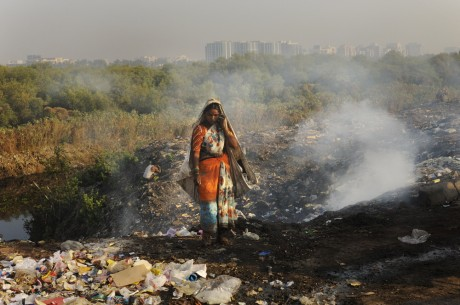 Woman picking over burning piles of rubbish on the edge of Mumbai's biggest slum, Dharavi, a thriving mix of poverty and enterprise that is home to over one million people - Mark Henley | Panos Pictures