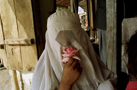 A woman wearing a white burqa holds a rose to her nose at a street market in Khwaja-Bahauddin - Yannis Kontos | Polaris | Panos Pictures