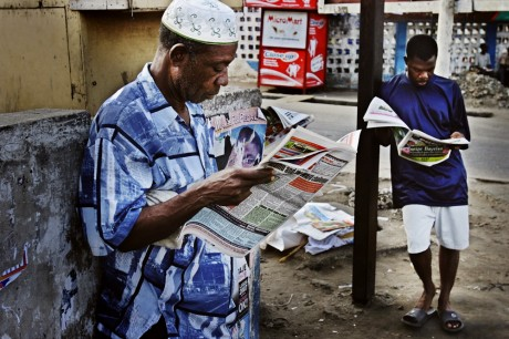 Two men read newspapers on the street of Lagos, Nigeria, on the day of presidential elections - Jacob Silberberg | Panos Pictures